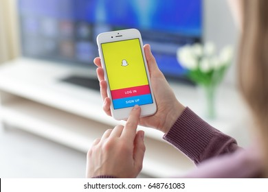 Alushta, Russia - May 23, 2017: Woman holding iPhone with social networking service Snapchat on the screen. iPhone was created and developed by the Apple inc.