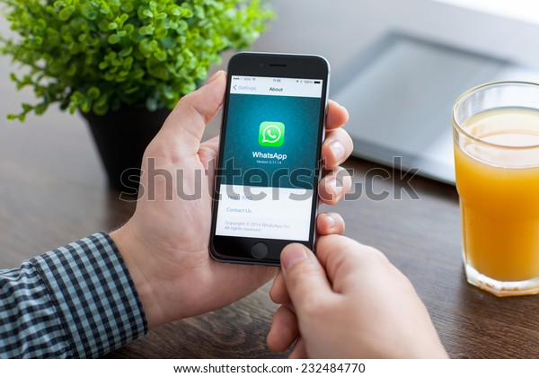 Alushta, Russia - November 21, 2014: Man holding a iPhone 6 Space Gray with social Internet service WhatsApp on the screen. iPhone 6 was created and developed by the Apple inc.