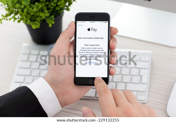 Alushta, Russia - November 3, 2014: Businessman holding a iPhone 6 Space Gray with service Apple Pay on the screen. iPhone 6 was created and developed by the Apple inc.