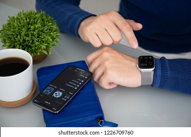 Alushta, Russia - November 3, 2018: Man hand with Apple Watch Series 4 and iPhone X on the table. Apple Watch was created and developed by the Apple inc.
