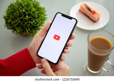 Alushta, Russia - November 6, 2018: Woman holding iPhone X with multinational entertainment company Google provides streaming media and video YouTube on the screen.