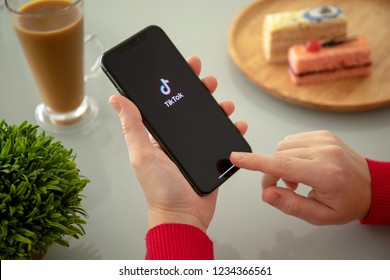 Alushta, Russia - November 6, 2018: Woman holding iPhone X with streaming service media and video TikTok on the screen. iPhone ten was created and developed by the Apple inc.