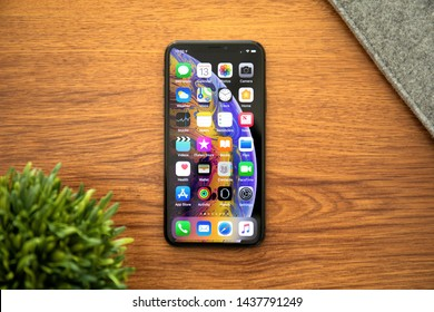 Alushta, Russia - October 13, 2018: iPhone X with home screen IOS on the table. iPhone 10 was created and developed by the Apple inc.