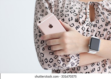 Alushta, Russia - October 22, 2015: Woman with Apple Watch in the hand holding iPhone 6 S Rose Gold. iPhone 6S and Watch was created and developed by the Apple inc.