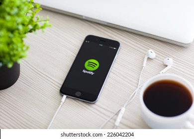 Alushta, Russia - October 24, 2014: Phone iPhone 6 Space Gray with music service Spotify on the screen on the table. iPhone 6 was created and developed by the Apple inc.