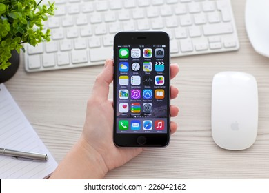 Alushta, Russia - October 25, 2014: Woman holding new phone iPhone 6 Space Gray over the table. iPhone 6 was created and developed by the Apple inc.