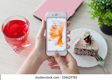 Alushta, Russia - October 25, 2015: Woman unlock phone iPhone6S Rose Gold over the table. iPhone 6S Rose Gold was created and developed by the Apple inc.