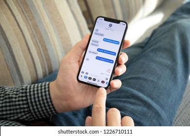 Alushta, Russia - October 9, 2018: Man hand holding iPhone X with social networking service iMessage on the screen. iPhone 10 was created and developed by the Apple inc.