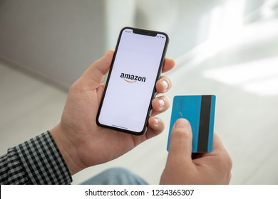 Alushta, Russia - October 9, 2018: Man holding iPhone X with Internet shopping service Amazon on the screen. iPhone 10 was created and developed by the Apple inc.