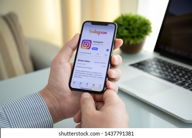 Alushta, Russia - October 9, 2018: Man hand holding iPhone X with social networking service Instagram on the screen. iPhone 10 was created and developed by the Apple inc.