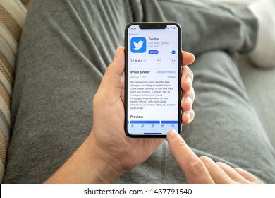 Alushta, Russia - October 9, 2018: Man hand holding iPhone X with social networking service Twitter on the screen. iPhone 10 was created and developed by the Apple inc.