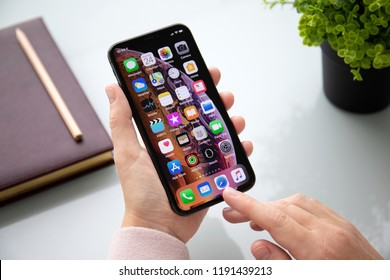Alushta, Russia - September 24, 2018: Woman hand holding iPhone X with home screen IOS. iPhone 10 was created and developed by the Apple inc.