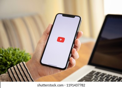 Alushta, Russia - September 26, 2018: Woman holding iPhone X with multinational entertainment company Google provides streaming media and video YouTube on the screen.