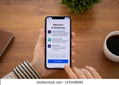 Alushta, Russia - September 26, 2018: Woman hand holding iPhone X with home screen Shortcuts app. iPhone 10 was created and developed by the Apple inc.