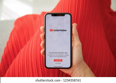 Alushta, Russia - September 27, 2018: Woman holding iPhone X with multinational entertainment company Google provides streaming media and video YouTube Premium on the screen.