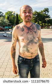 Alushta, Russia-May 13, 2018: Unknown man-tramp covered with tattoos on the embankment of the city.