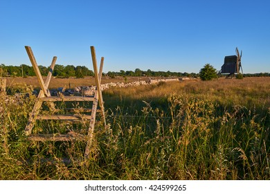 Alvar limestone moor with fence and old windmill in sunset at Isle if Oeland, province Kalmar, Sweden