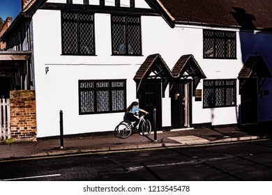 Alvechurch Worcestershire Midlands Engand UK October 27th. 2018 Teenage girl on bicycle outside old sunlit house in an english village