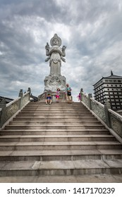 ALVKARLEBY, SWEDEN - JULY 27, 2014: Low angle view of a family at Dragon Gate on stone steps next to a large Chinese statue with dramatic sky and building in the background. Alvkarleby July 27, 2014.