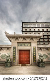 ALVKARLEBY, SWEDEN - JULY 27, 2014: Front view of a traditional Chinese building at Dragon Gate. Red entrance door with lion statues, hotel building and dark clouds at Alvkarleby Sweden July 27, 2014.