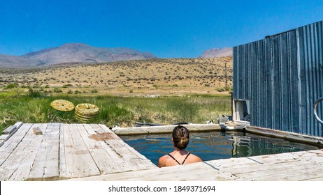 Alvord, Oregon, USA - June 23rd 2018: Young woman soaking in the Alvord Desert Hot spring in southeastern Oregon, with view on the Steens mountain