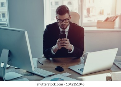 Always available. Handsome young man in formalwear using his smart phone while sitting in the office
