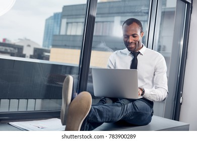 Always busy. Full length of positive pleasant african businessman is sitting on windowsill with his laptop on his knees. He is looking at monitor with smile while typing text on keyboard. Copy space