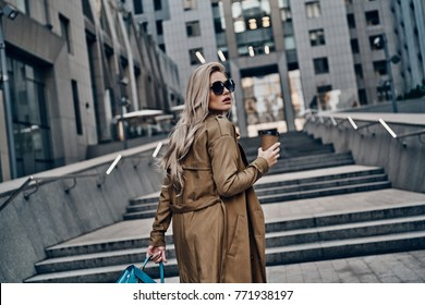 Always confident in her style. Attractive young woman drinking coffee while walking up the steps outdoors