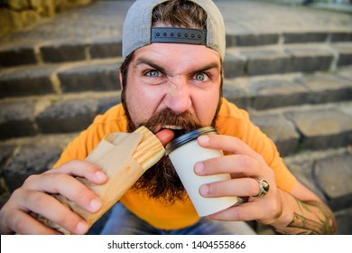 Always fresh and tasty hot dog. Hungry guy biting hot dog and sipping coffee. Bearded man eating unhealthy hot dog sandwich with beverage. Hipster drinking and eating hot dog during rest break.