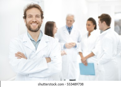 Always here to help. Handsome mature bearded doctor smiling confidently with his arms crossed his medical team on the background healthcare happiness trust success confidence wellbeing medicine