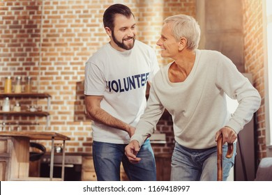 Always here. Satisfied paralyzed aged man trying to stand with help of a cane looking at a volunteer and smiling.