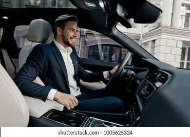 Always in a hurry. Handsome young man in full suit smiling while driving a car