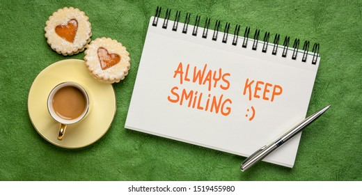 always keep smiling inspirational handwriting in a sketchbook, flat lay with coffee and heart cookies, optimism, kindness and positivity concept