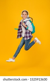 Always in motion. Energetic cheerful teen listening music. Stylish schoolgirl going to school. Girl little fashionable girl carry backpack. School daily life. Happy carefree child. School and leisure.