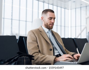 Always on the go. Portrait of handsome smiling businessman in formalwear holding a laptop with earphones while sitting in the airport