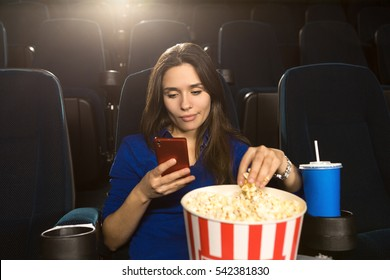 Always on her phone. Gorgeous mature woman looking bored at the movies sitting alone at the cinema auditorium surfing internet on her smart phone boredom unhappy digital connection hobby concept