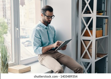 Always online. Young modern businessman working using digital tablet while sitting on the window sill in the office