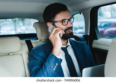 Always ready for business. Handsome young businessman using laptop and talking on mobile phone while sitting in car