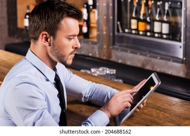 Always staying in touch. Confident young man in shirt and tie sitting at the bar counter and working on digital tablet