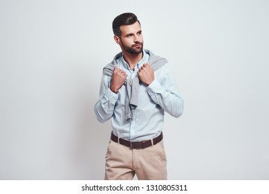 Always in style. Close-up portrait of stylish and elegant bearded man thinking about something and looking away while standing on a grey background. Fashion look.