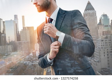 Always in style. Fashionable businessman adjusting sleeve while standing outdoors with cityscape on the background