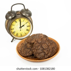 Always time for cookies: represented by orange plate of homemade chocolate brownie cookies and a brass colored vintage alarm clock against a white background.