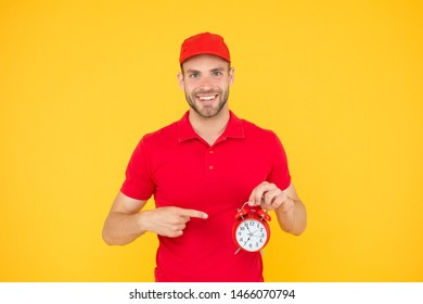Always in time. Happy man with alarm clock on yellow background. Delivering your purchase. Courier service delivery. Salesman and courier career. Courier and delivery service. Postman delivery worker.