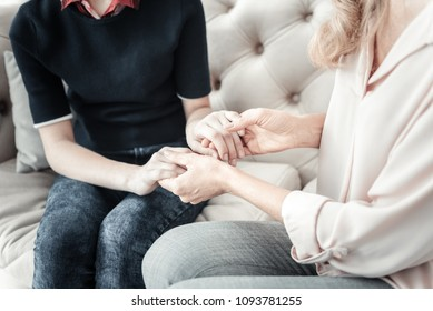 Always together. Reliable lovely caring natives sitting on the sofa spending time together holding by hands.