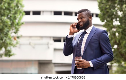 Always In Touch. African American Businessman Talking On Mobile Phone During Coffee Break In City. Free space
