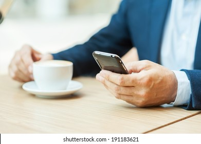 Always in touch. Cropped image of man in formalwear drinking coffee and typing a message on mobile phone while sitting in restaurant