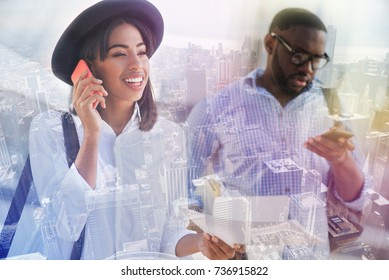 Always in touch. Positive smiling african american woman talking on phone and standing with a handsome guy while expressing joy