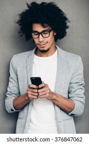 Always in touch.Handsome young African man holding smart phone and looking at it while standing against grey background