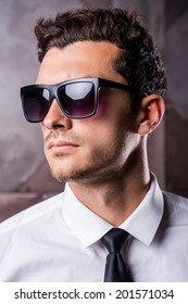 Always trendy. Confident young man in formalwear and sunglasses looking away while standing against metal background