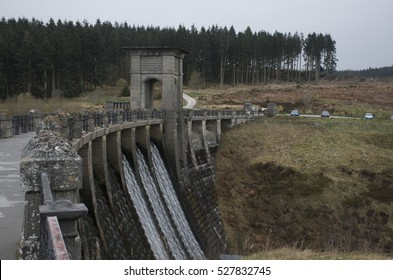 Alwen reservoir, Wales, UK Autumn day showing entire dam with water flowing and forest.